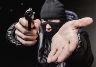 銃を突き出して金を要求する強盗