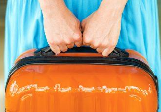 鏡面加工のスーツケースを持つ女性