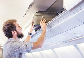 機内で荷物を収納する男性