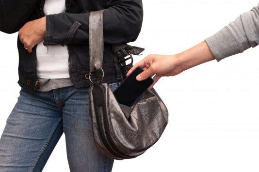 財布をすろうとするスリ